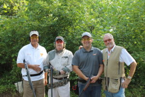 4 men clay shooting and smiling with guns